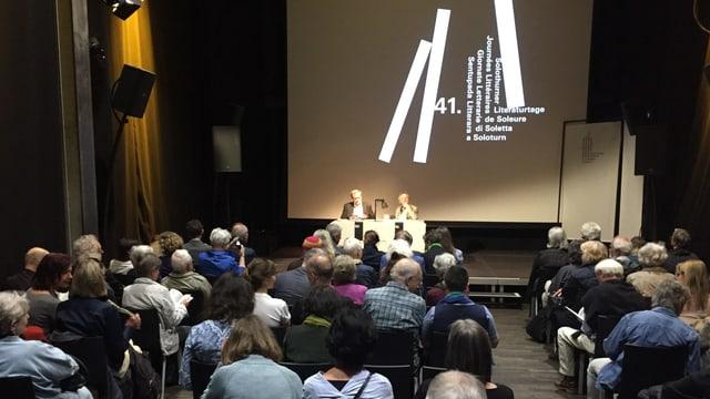 Ein Saal, gefüllt mit Menschen, die dem Schriftsteller Ernst Halter, ganz klein am Ende des Saales, zuhören.