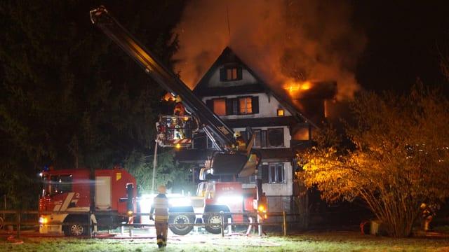 Feuerwehrleute löschen in Zug ein Holzhaus, das in Vollbrand steht.