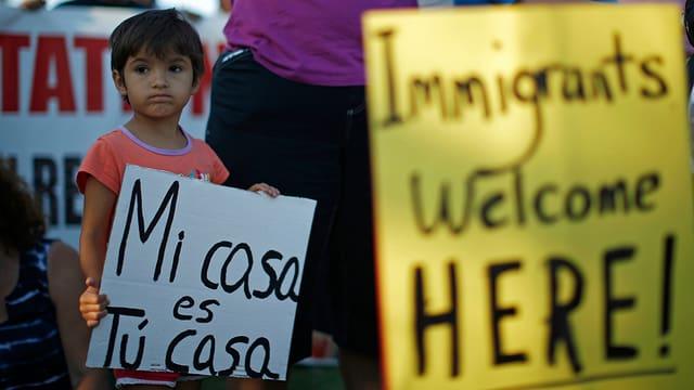 Demonstranten tragen Transparente mit der Aufschrift «Migranten sind hier willkommen».