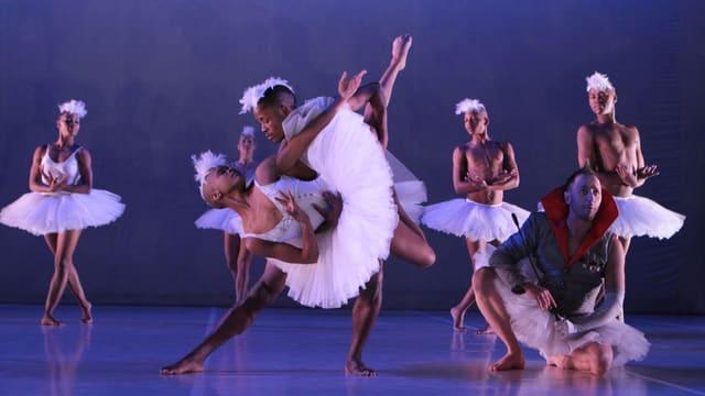 Afrikanische Tänzerinnen und Tänzer in weissen Ballet-Tutus, im Vordergrund eine Tänzerin und ein Tänzer (er auch in einem Tutu) beim Pas de deux.
