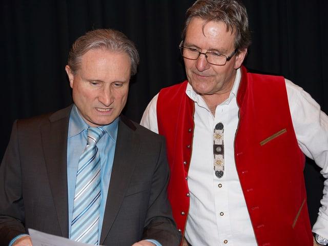 Zwei Männer stehen nebeneinander und blicken auf ein Manuskript.