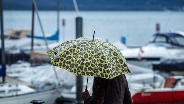 Ina persuna cun parasol a la riva dal Lago Maggiore.