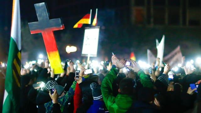 Eine Menschenmenge in der Nacht. Die Leute halten ihre Handys hoch. Im Bildmittelgrund hält ein Pegida-Demonstrant in Dresden ein mannshohes Kreuz in den Landesfarben in die Höhe.