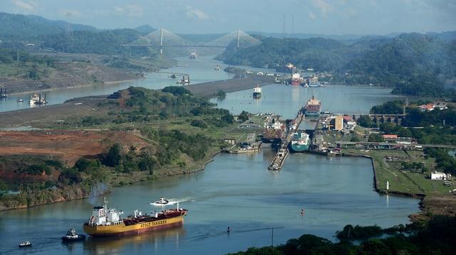 Aufnahme von oben: Ein Frachter wartet auf die Einfahrt in die Schleuse, dort werden bereits mehrere Schiffe abgefertigt, in der Ferne eine zweite Schleuse mit Schiffen.