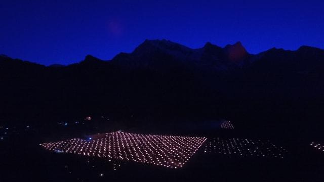 Nachtbild mit regelmässigen Lichtpunkten. Im Hintergrund Berge.
