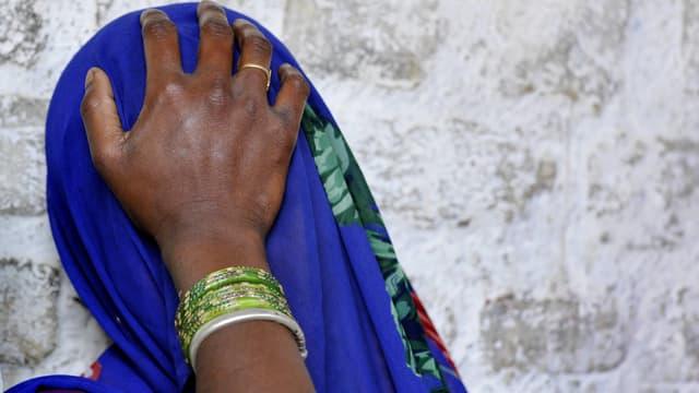 Eine Frau hat ihre blaue Sari über das Gesicht gezogen und hält die Hand an die Stirn.