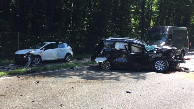 Zwei völlig kaputte Autos stehen auf einer Strasse.