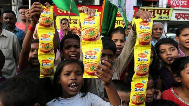 Indische Kinder halten Nudelpackungen von Nestlé in die Höhe und protestieren.