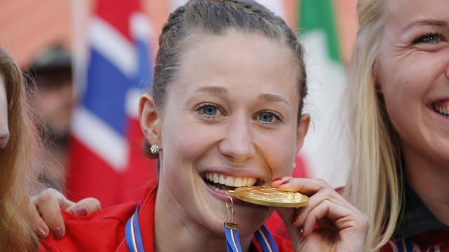 Judith Wyder beisst auf ihre WM-Goldmedaille, die um ihren Hals hängt.