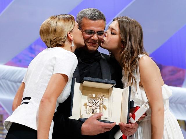 Zwei Frauen küssen einen Mann auf die Wange, der die Goldene Palme in den Händen hält