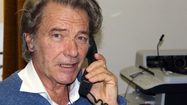 Ein Mann in einem Büro mit Telefonhörer in der Hand.