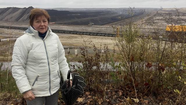 Eine Frau vor einer öden, zerfurchten Landschaft.