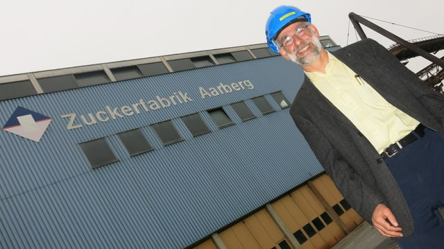 Ein Mann mit Helm vor einem grossen Fabrikgebäude.