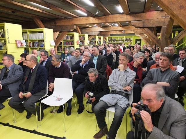 Blick ins Publikum, in der Kantonsbibliothek Baselland. Der Raum ist eng bestuhlt.