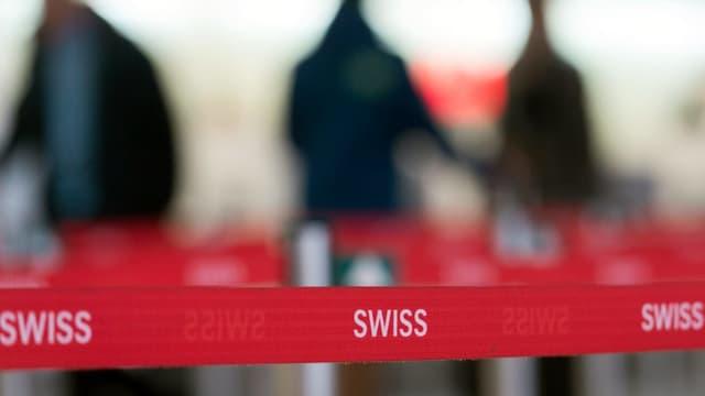 Purtret d'in bindel cun scrit si Swiss e persunas davostier che n'èn betg en il focus da la camera.