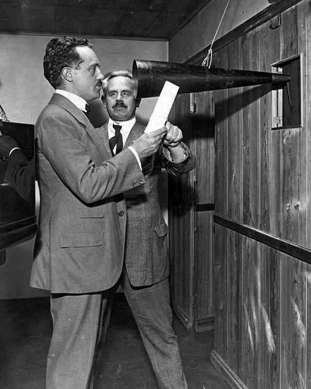 Zwei Männer in Anzügen. Der einen hält einen Text vor sich und spricht in einen grossen Trichter.