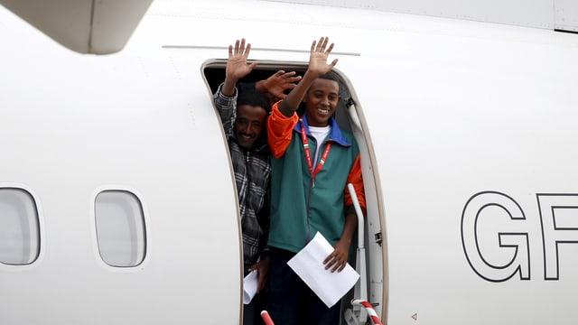 Zwei Flüchtlinge stehen an der Flugzeugtüre und winken