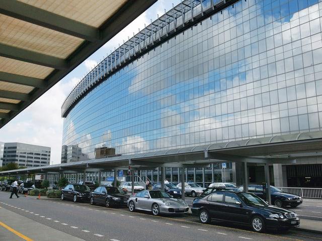 Mehrere schwarze Autos parkieren vor einem Gebäude mit Glasfassade