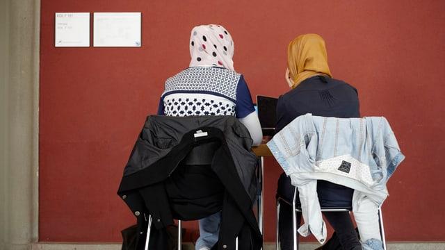 Symbolbild: Zwei Frauen mit Kopftuch sitzen auf Stühlen, mit dem Rücken gegen den Fotografen.