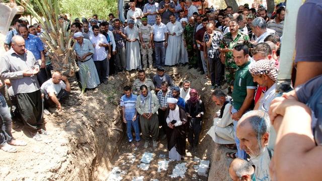 Dutzende Männer stehen um das Grab und trauern um die Opfer.