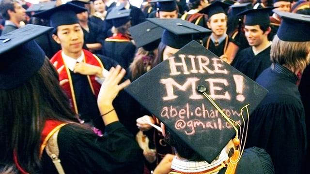 Auf dem Doktorhut eines Studenten steht in grossen Buchstaben «Stellt mich ein!» und seine Email-Adresse.