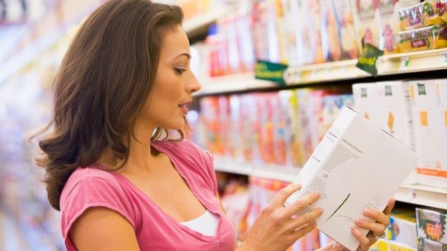 Eine Frau studiert eine Lebensmittelverpackung im Geschäft