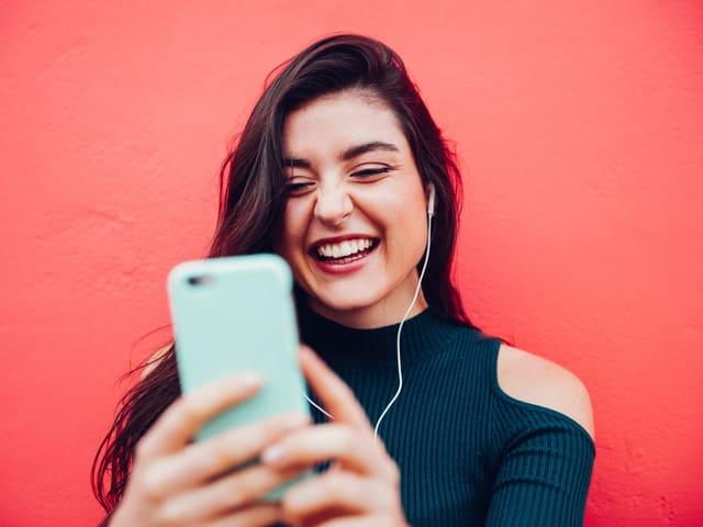 Ein Bild einer jungen Frau, die mit ihrem Smartphone ein Selfie aufnimmt.