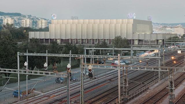 Visualisierung der neuen Eishockeyarena von aussen mit Bahngleisen im Vordergrund.