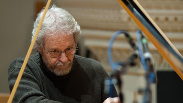 Georg F. Senn sitzt mit einem Werkzeug am Klavier
