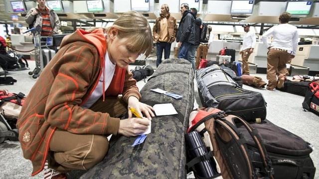 Snowboarderin mit ihrem Spezialgepäck am Flughafen-Check-In
