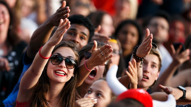 Zu sehen ist eine Menschenpulk. Die Frauen und Männer gucken augenscheinlich einem Fussballspiel an einem Public Viewing zu und verwerfen die Hände.