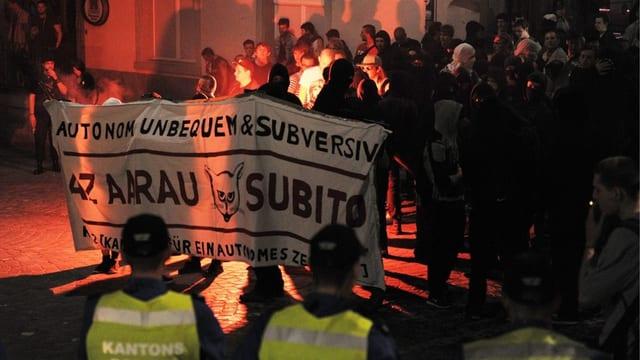 Demonstranten mit einem Transparent vor zwei Polizisten