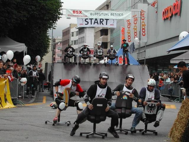 Bürostuhlrennen in Olten. 4 Personen sitzen mit Helmen auf Stühlen und fahren. Oben zu sehen: Die Rampe mit 4 weiteren Teilnehmern.