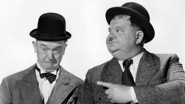 Schwarzweissfoto: Zwei Männer in grauen Anzügen und mit kleinen schwarzen Hüten.