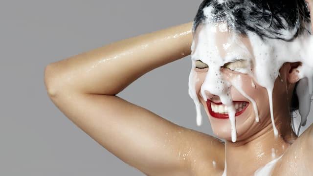 Eine Frau wäscht sich lachend die Haare.