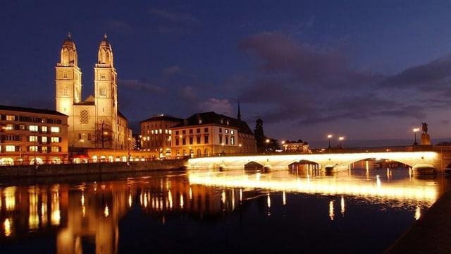 Eine am Abendhimmel hell erleuchtete Münsterbrücke mit dem Grossmünster auf der linken Seite
