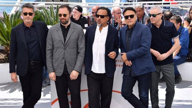 Fünf Männer mit Sonnenbrille auf dem Roten teppich.