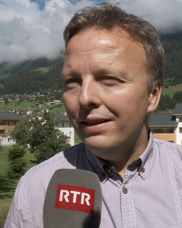 Gerard Carigiet avant in microfon dad RTR. Davostiers breil e parts da las chasas da lain e paraid alva dal resort Pradas.