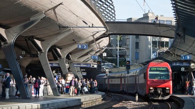 S-Bahn-Zug mit roter Front und blau weissen Wagen im Bahnhof Stadelhofen.