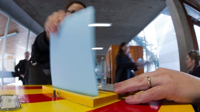 Eine Stimmbürgerin wirft ihren Stimmzettel in eine rot-gelbe Wahlurne.