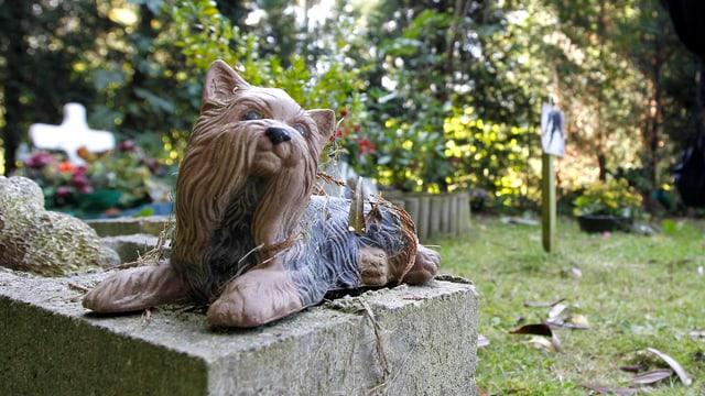 Eine Statue eines langhaarigen sitzenden Hundes auf einem Grab im Tierfriedhof im belgischen Ort Boom.