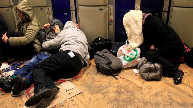 Quatter persunas schain per terra ad ina staziun da tren ed han cuvert il chau cun in lenziel.