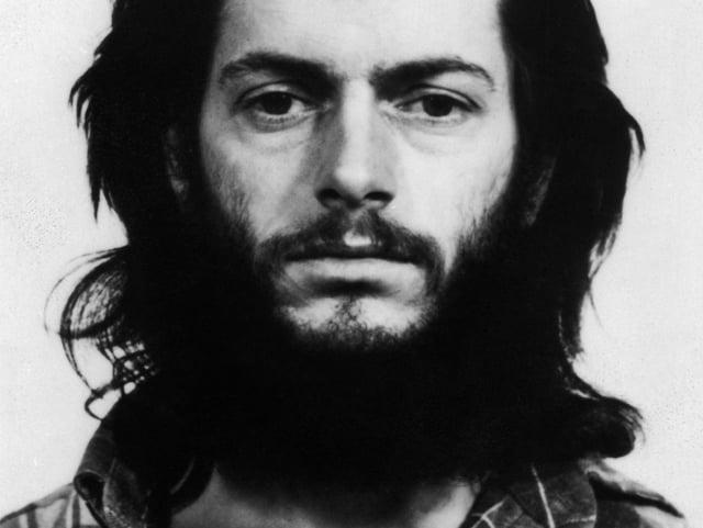 Ein Mann mit dunklen, schulterlangen Haaren und Bart blickt in die Kamera.