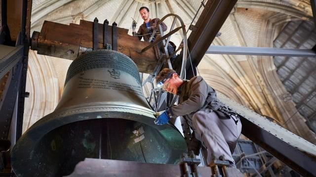 Männer arbeiten an einer grossen Kirchenglocke, die in einem Turm hängt.