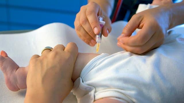 Hände einer Ärztin, die ein Baby impft.