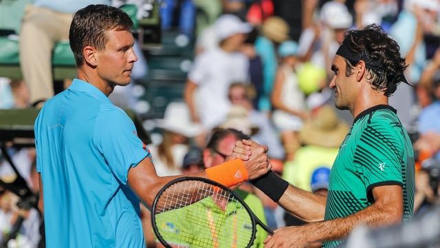 Tomas Berdych schüttelt am Netz Roger Federer die Hand.