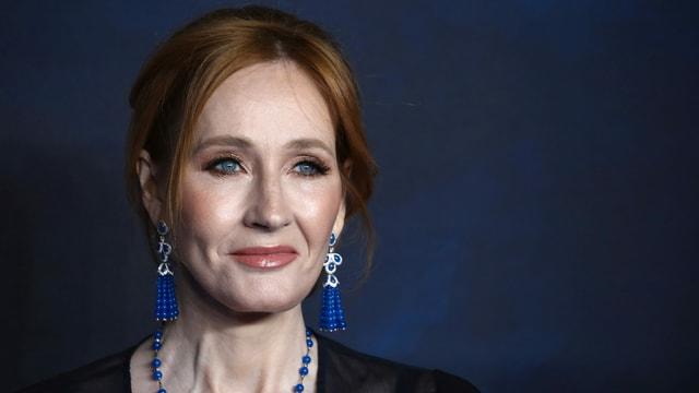 Eine rothaarige  Frau mit blauen Ohrringen.