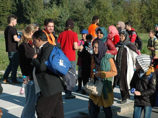 Die Helfer verteilen Trinkflaschen an den Strom von Flüchtlingen.