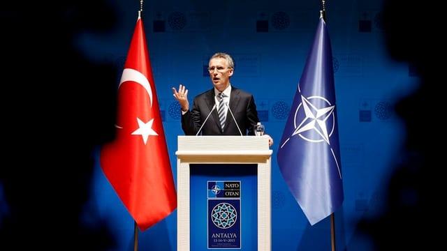 Stoltenberg an einem Rednerpult, links eune türkische, rechts eine Nato-Fahne.