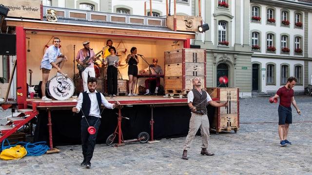 Ein Zirkuswagen mit verschiedenen Musikern und Künstlern.